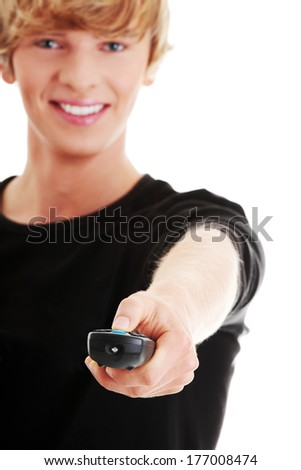 Young caucasian man changing channels with remote control , isolated on white  - stock photo
