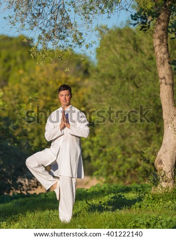 young caucasian man doing yoga in the park, selective focus - stock photo