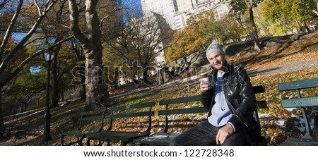 Young Caucasian Man enjoying his cup of hot coffee on the sunny day in Central Park, New York city. Autumn - stock photo