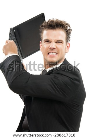 Young Caucasian man furious throwing laptop indoors over white background. - stock photo