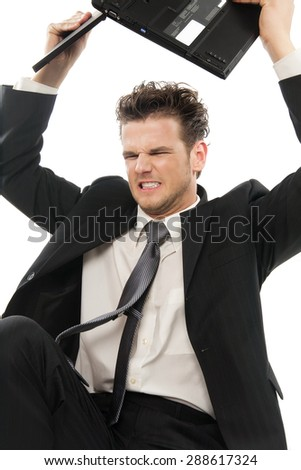 Young Caucasian man furious throwing laptop indoors over white background.