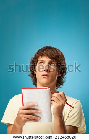 Young Caucasian man holding a notebook and a pencil.