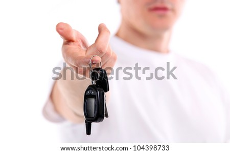 Young caucasian man holding car key. Image with shallow depth of field, the key is in focus.