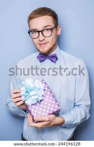 Young caucasian man holding colorful gift. Present, birthday, Valentine. Studio portrait over blue background   - stock photo