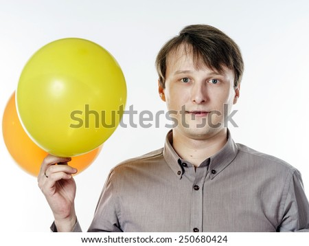Young caucasian man holding yellow air balloons in his hand. Happy like a child. - stock photo