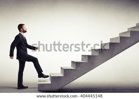 Young Caucasian man in a formal wear start climbing concrete stairs, side view