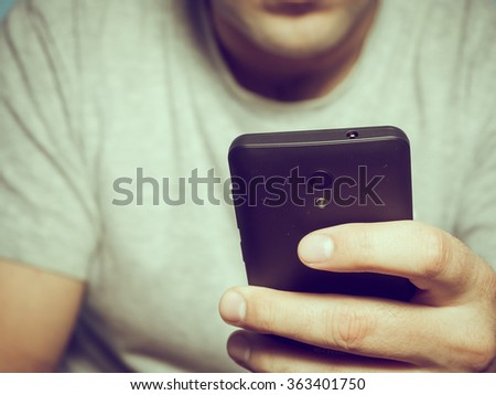 Young caucasian man in a gray t-shirt smartphone indoors. - stock photo