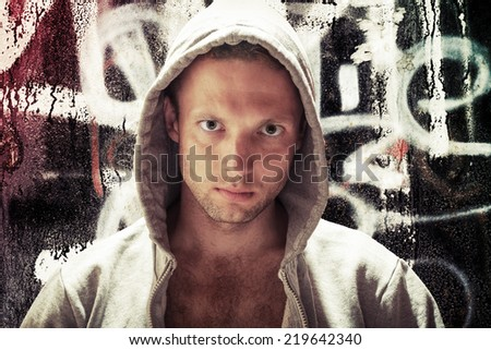 Young Caucasian man in hood, street artist portrait with grungy graffiti wall on background, toned effect - stock photo