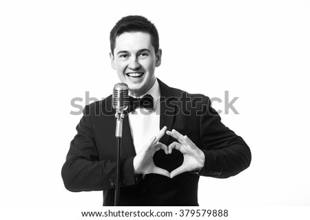 Young caucasian man in suit singing with the microphone and make love sign with hands. Isolated on white background. Monochrome photography. Singer concept. - stock photo