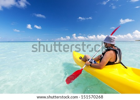 Young caucasian man kayaking in sea at Maldives  - stock photo