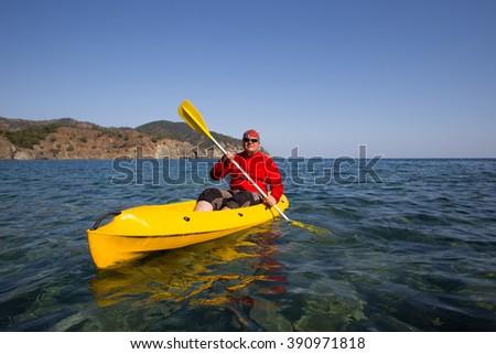 Young caucasian man kayaking in sea at Maldives - stock photo