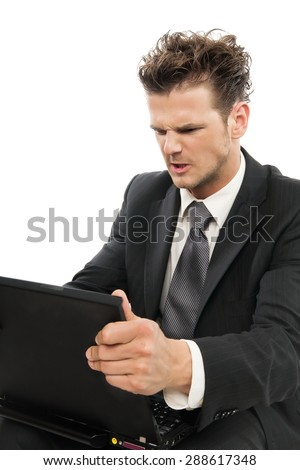 Young Caucasian man looking desperate with laptop indoors over white background. - stock photo