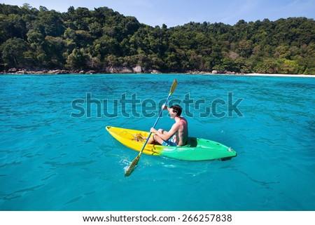 young caucasian man on kayak near paradise island in turquoise water - stock photo