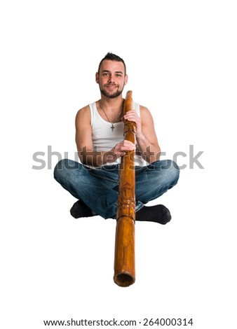 young caucasian man play music on his didgeridoo (Australian national musical instrument) - stock photo
