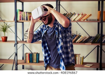 Young Caucasian man playing computer game in white virtual reality headset glasses