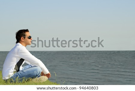 young caucasian man sitting alone and looking to the sea - stock photo