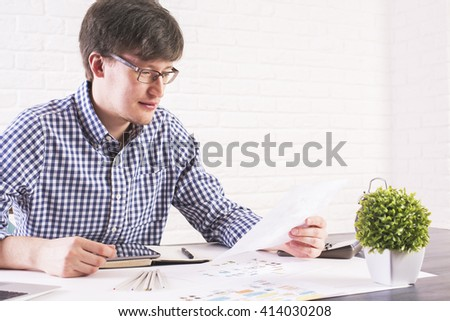 Young caucasian man sitting at office desk with business sketch and plant and looking at paper sheet - stock photo
