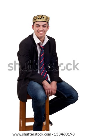 Young caucasian man sitting on the chair with indian hat on head - stock photo