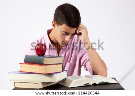 Young Caucasian man studying books for school, with a red apple sitting on top of his stack of books.