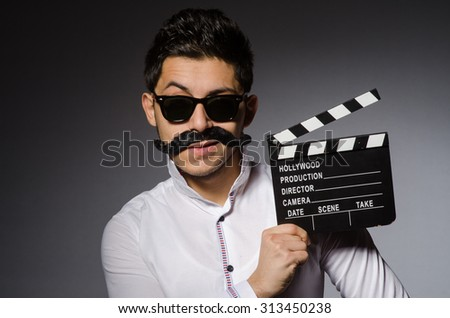 Young caucasian man with clapperboard against gray - stock photo