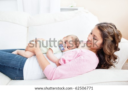 Young caucasian mother taking care of her baby lying on the sofa - stock photo