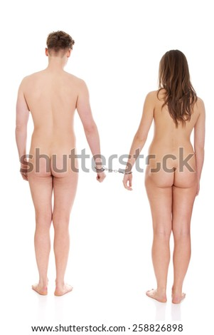 Young caucasian nude couple handcuffed. - stock photo
