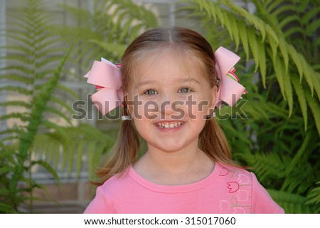 Young caucasian preschool age girl smiling wearing pink hair bows and a pink shirt with green fern plants in the background - stock photo