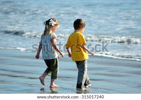 Young caucasian preschool boy and girl, brother and sister, walking on the beach to see waves for the first time - stock photo