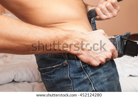 Young Caucasian sporty man takes off his blue jeans, close-up photo