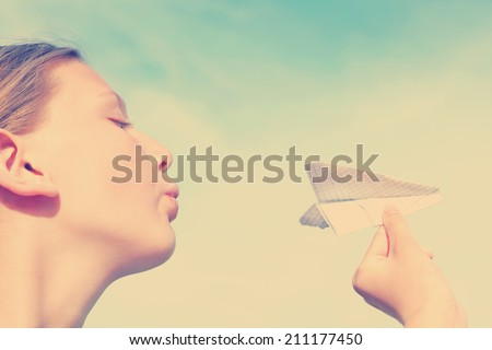 Young caucasian teenager girl with paper plane in the hand done with a vintage retro instagram filter - stock photo