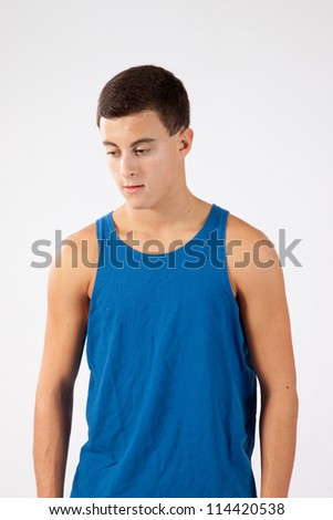 Young Caucasian teenager in a blue muscle shirt, looking down and thinking