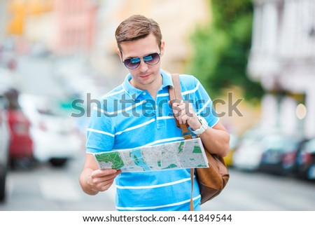 Young caucasian tourist with a city map and backpack in Europe. Happy guy looking at the map of European city in search of attractions. - stock photo