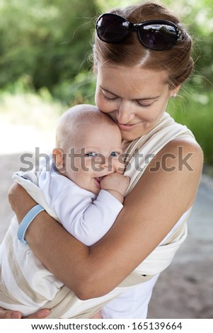 Young Caucasian woman and her baby son in sling outdoors - stock photo