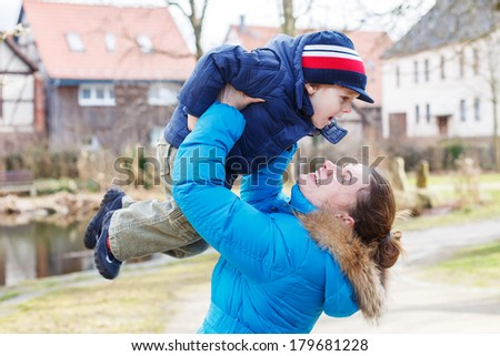 Young caucasian woman and her little adorable son having fun, outdoors on cold day. - stock photo