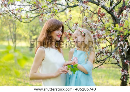 Young caucasian woman and her little daughter looking to each other in spring garden - stock photo