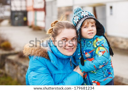 Young caucasian woman and her little son hugging on bridge, outdoors on cold day. - stock photo