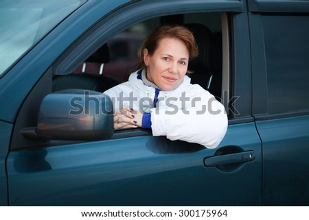 Young Caucasian woman as a driver in a big car, outdoor portrait - stock photo