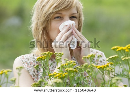 Young Caucasian woman blowing nose into tissue in front of flowers - stock photo