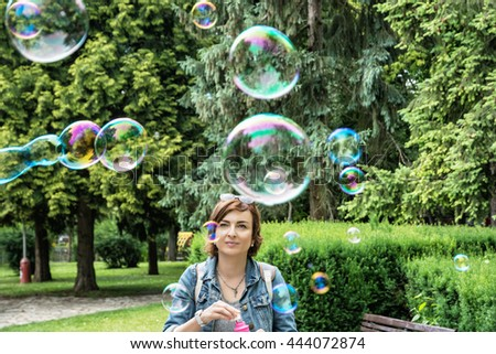 Young caucasian woman blowing soap bubbles in the city park. Leisure activity. Natural beauty. Outdoor activity. Summer holiday. - stock photo