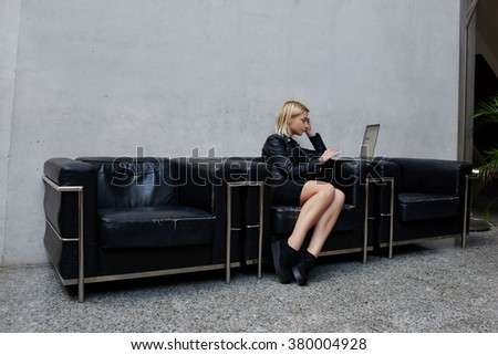 Young Caucasian woman checks the work of her employees on laptop computer while sitting in modern office interior, female with trendy look reading fashion news on portable net-book during work break - stock photo