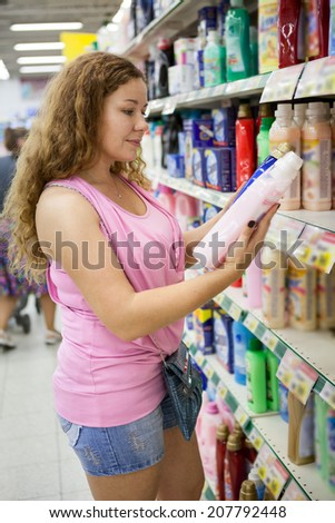 Young Caucasian woman choosing cleaning detergent in shop - stock photo