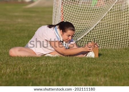Young Caucasian woman doing warmup stretches outside in a grassy area behind a sports field. - stock photo