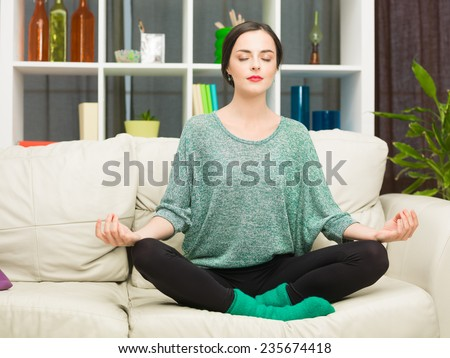 young caucasian woman doing yoga on sofa at home. lotus pose - stock photo