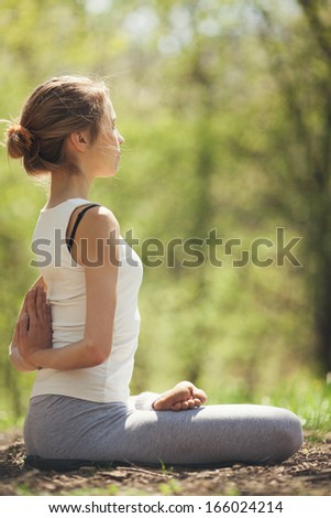 Young Caucasian woman doing yoga outdoors.