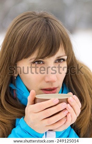 Young caucasian woman drinking hot coffee or tea at winter outdoor. Pretty girl tasting drink - stock photo