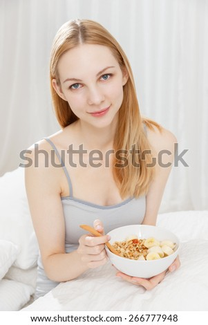 Young Caucasian woman eating breakfast on the bed - stock photo