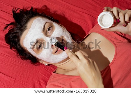Young caucasian woman having a white smoothing face mask. - stock photo