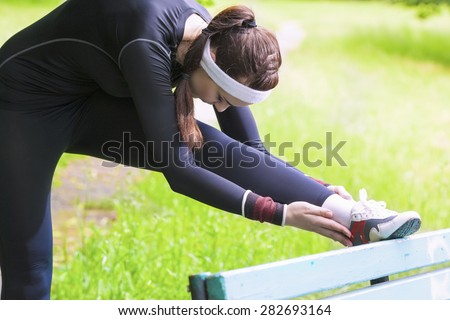 Young Caucasian Woman Having Stretching Exercises Outdoors. Horizontal Image Orientation - stock photo