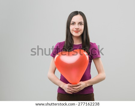 young caucasian woman holding heart shaped balloon and smiling. copy space available - stock photo
