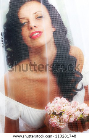 Young Caucasian woman in a white dress behind a veil with flowers. - stock photo